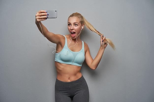 Aantrekkelijke sportieve jonge blonde vrouw met paardenstaart kapsel trekt haar haren terwijl ze over de lichtgrijze achtergrond staat, vrolijk kijkend naar de camera met brede mond geopend tijdens het maken van selfie