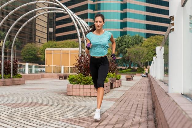 Aantrekkelijke sportieve jonge vrouw die op bestrating loopt