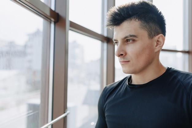 Aantrekkelijke sportieve man bij het raam. atleet poseren in de buurt van ruime ramen. sportschool en sport.