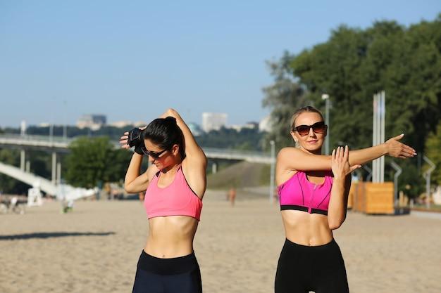 Aantrekkelijke sportieve meisjes in zonnebril die zich uitstrekken op het strand in de ochtend