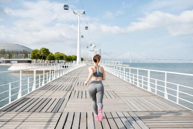 Aantrekkelijke sportieve vrouw die op de brug rijdt