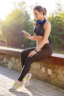 Aantrekkelijke sportieve vrouw die smartphone met hoofdtelefoons in het ochtendpark gebruiken