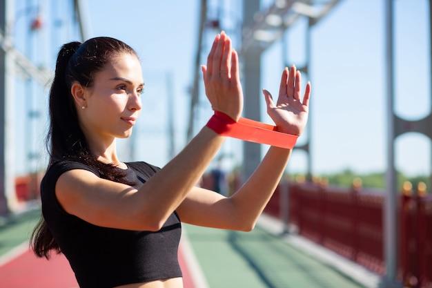 Aantrekkelijke sportieve vrouw doet training met rubberen weerstandsband op een brug. ruimte voor tekst