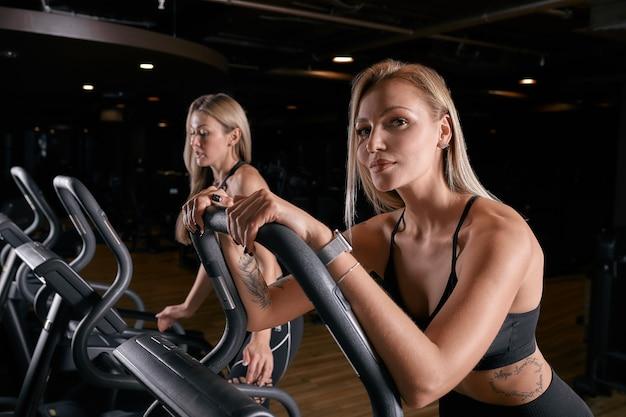 Aantrekkelijke sportieve vrouwen die hometrainers berijden tijdens fietstraining in gymnastiek