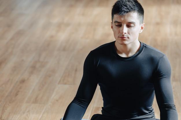 Aantrekkelijke sportman die yoga doet. serre en schaduwen. sportschool en sport.