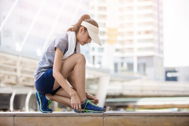 Aantrekkelijke sportvrouw die haar schoenveter knoopt en zich klaar maakt om te rennen in de stedelijke stad