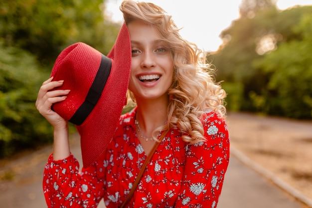 Aantrekkelijke stijlvolle blonde glimlachende vrouw in stro rode hoed en blouse zomer mode-outfit