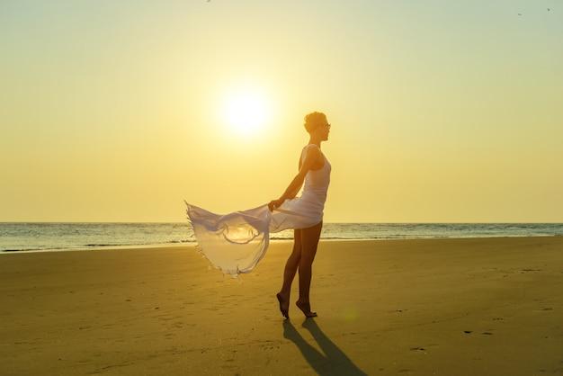 Aantrekkelijke stijlvolle blonde in zonnebril en licht witte jurk staat op blote voeten op geel zand op het strand