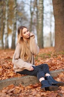 Aantrekkelijke stijlvolle blonde lachende jonge vrouw, gekleed in gezellige trui, trendy zwarte jeans en zwart lederen laarzen zitten in herfst park.