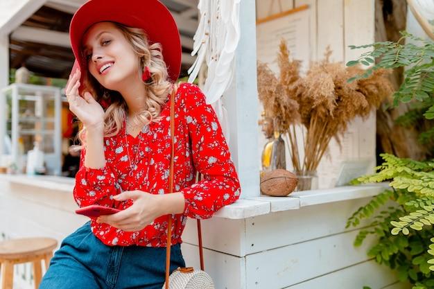 Aantrekkelijke stijlvolle blonde lachende vrouw in rode strooien hoed en blouse zomer mode outfit café met behulp van telefoon