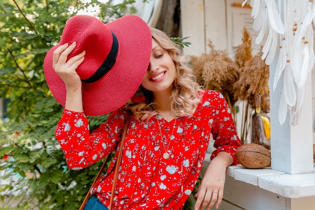 Aantrekkelijke stijlvolle blonde lachende vrouw in rode strooien hoed en blouse zomer mode outfit café