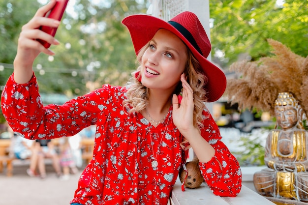 Aantrekkelijke stijlvolle blonde lachende vrouw in rode strooien hoed en blouse zomer mode outfit selfie foto nemen op camera slimme telefoon café