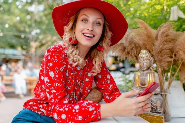 Aantrekkelijke stijlvolle blonde lachende vrouw in stro rode hoed en blouse zomer mode outfit bedrijf met behulp van slimme telefoon café