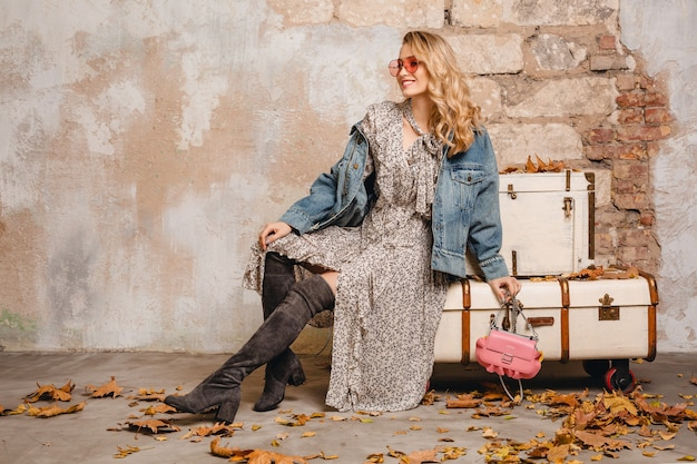 Aantrekkelijke stijlvolle blonde vrouw in spijkerbroek en oversized jas lopen tegen de muur in de straat