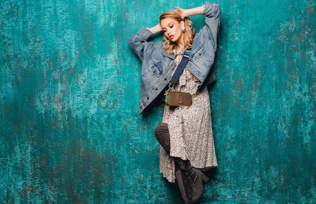 Aantrekkelijke stijlvolle blonde vrouw in spijkerbroek en oversized jas lopen tegen vintage groene muur in straat