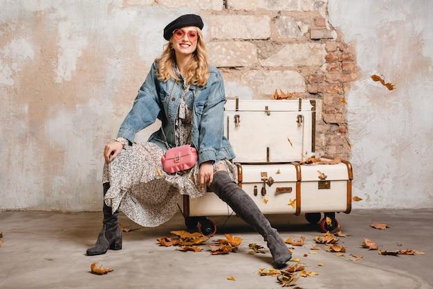 Aantrekkelijke stijlvolle blonde vrouw in spijkerbroek en oversized jas poseren tegen muur in straat