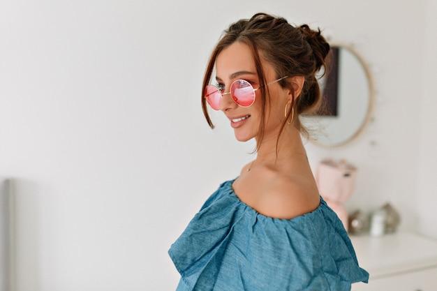 Aantrekkelijke stijlvolle brunette vrouw met verzameld haar blauwe top en roze bril dragen