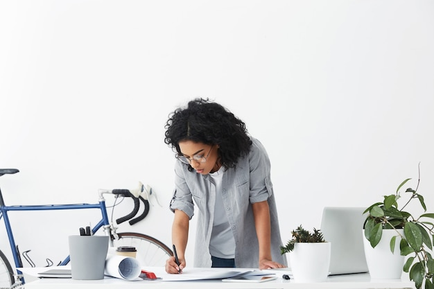 Aantrekkelijke stijlvolle gemengd ras vrouwelijke hoofdingenieur in ronde glazen staande boven haar witte bureau