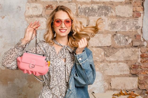 Aantrekkelijke stijlvolle glimlachende blonde vrouw die in jeansjasje tegen muur in straat loopt