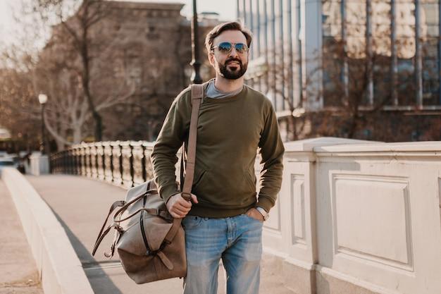 Aantrekkelijke stijlvolle hipster man wandelen in de stad straat met lederen tas sweatshot en zonnebril dragen, stedelijke stijltrend, zonnige dag