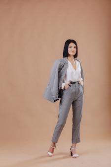Aantrekkelijke stijlvolle jong meisje in zakelijke kleding die zich voordeed op crème muur. concept van stijlvolle kleding en verfijning.