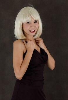 Aantrekkelijke stijlvolle jonge aziatische vrouw in blonde pruik en zwarte jurk met blauw gekleurde nagels glimlachen en kijken naar camera tegen grijze achtergrond