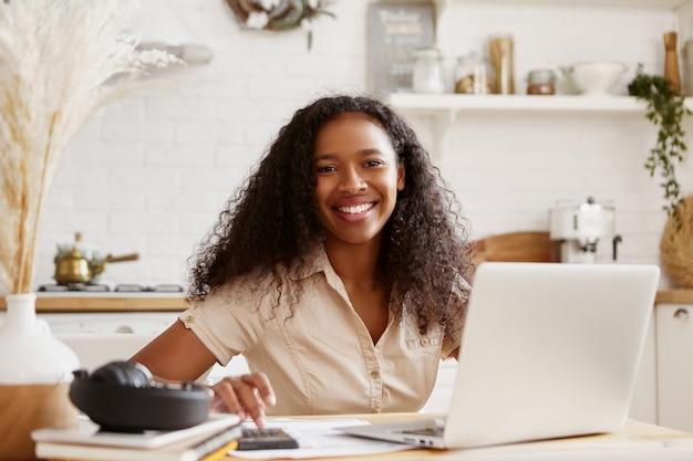 Aantrekkelijke stijlvolle jonge donkere vrouw in beige overhemd zittend aan de keukentafel, met behulp van laptop, budget berekenen, vakantie plannen, gelukkig lachend. zelfstandige zwarte vrouw die vanuit huis werkt