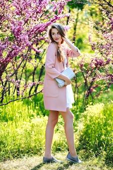 Aantrekkelijke stijlvolle jonge vrouw in lichte witte jurk, roze jas, met lang haar wandelen in de tuin met bloeiende sakura