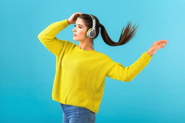 Aantrekkelijke stijlvolle jonge vrouw luisteren naar muziek in draadloze koptelefoon gelukkig gele gebreide trui dragen