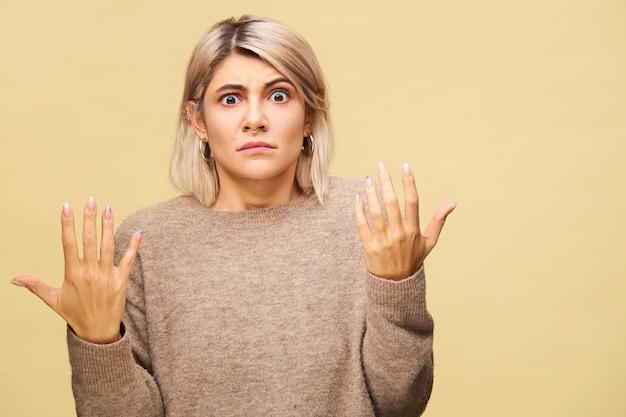 Aantrekkelijke stijlvolle jonge vrouw met blond bob kapsel emotioneel gebaren met verontwaardigde gelaatsuitdrukking, schouders ophalen, verward of verontwaardigd voelen. menselijke reactie en gevoelens