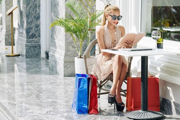 Aantrekkelijke stijlvolle jonge vrouw zittend aan tafel op terras met boodschappentassen, wijn drinken en schrijven in de planner