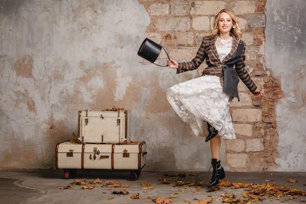 Aantrekkelijke stijlvolle lachende blonde vrouw in geruit jasje lopen tegen muur in straat