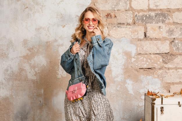 Aantrekkelijke stijlvolle lachende blonde vrouw in spijkerbroek en oversized jas lopen tegen de muur in de straat