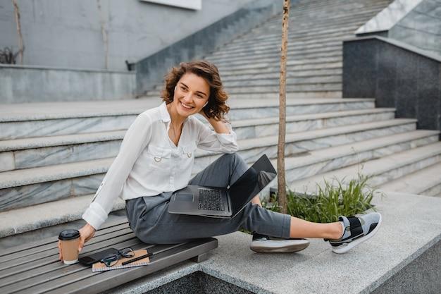 Aantrekkelijke stijlvolle lachende vrouw die typt op laptop