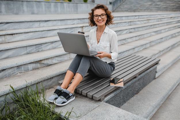 Aantrekkelijke stijlvolle lachende vrouw in glazen werken typen op laptop