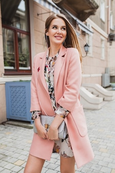 Aantrekkelijke stijlvolle lachende vrouw lopen stad straat in roze jas lente modetrend bedrijf portemonnee, luisteren naar muziek op oortelefoons
