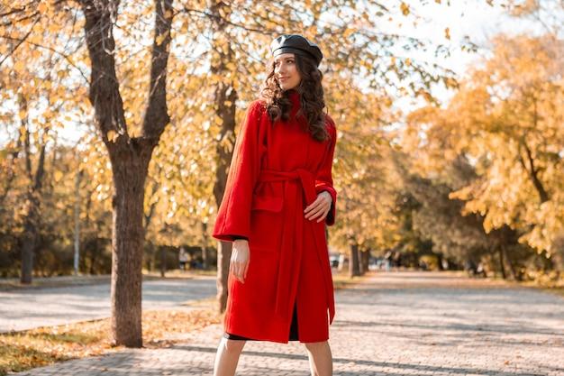 Aantrekkelijke stijlvolle lachende vrouw met krullend haar wandelen in park gekleed in warme rode jas herfst trendy mode, streetstyle, baret hoed dragen