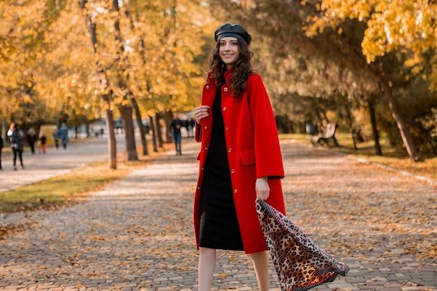 Aantrekkelijke stijlvolle lachende vrouw met krullend haar wandelen in park gekleed in warme rode jas herfst trendy mode, streetstyle, baret hoed en luipaard gedrukte sjaal dragen