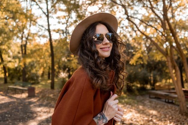 Aantrekkelijke stijlvolle lachende vrouw met krullend haar wandelen in straat park gekleed in warme bruine jas herfst trendy mode, streetstyle hoed en zonnebril dragen
