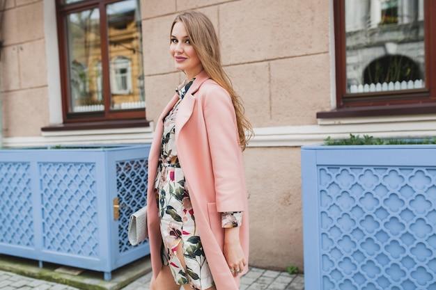 Aantrekkelijke stijlvolle lachende vrouw stad straat lopen in roze jas lente modetrend draaien