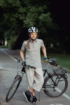 Aantrekkelijke stijlvolle man poseren naast zijn fiets op het park. hij houdt zijn fiets vast.