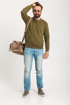 Aantrekkelijke stijlvolle man reiziger geïsoleerd staande met tas knap gekleed in spijkerbroek en sweatshot volle hoogte