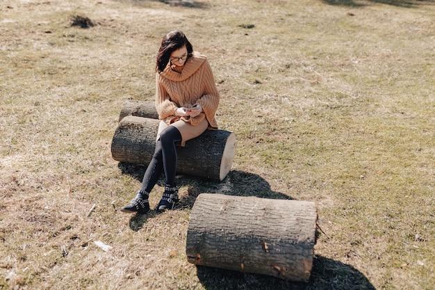 Aantrekkelijke stijlvolle meisje op aard op bos achtergrond met telefoon op een zonnige dag