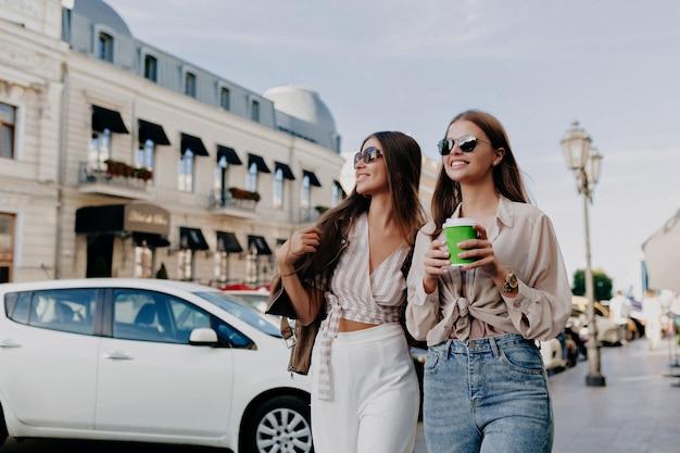 Aantrekkelijke stijlvolle modellen die met een pratende koffie lopen, hebben plezier in de stad op de achtergrond