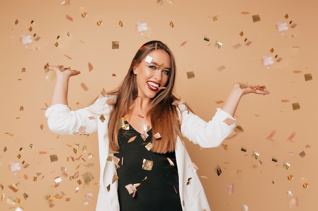Aantrekkelijke stijlvolle mooie vrouw met lichtbruin haar en lichte make-up dragen zwarte jurk en witte jas poseren op beige muur met confetti, ware gelukkige emoties, vakantie, feest, verjaardag