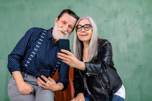 Aantrekkelijke stijlvolle paar, bebaarde man en grijze haren dame, samen zitten op de rode stoel en het gebruik van de telefoon apps, kijken naar het scherm van de smartphone en glimlachen