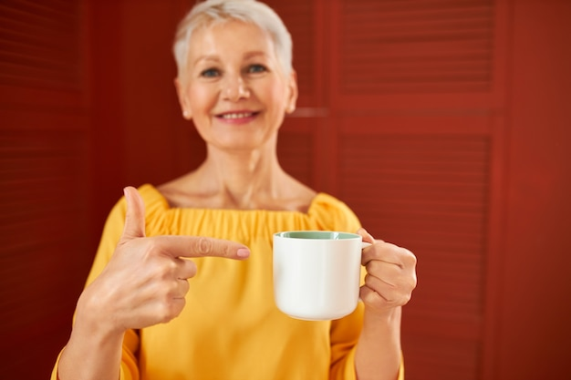 Aantrekkelijke stijlvolle rijpe blonde vrouwelijke gepensioneerde m / v in gele jurk 's ochtends koffie drinken, wijsvinger wijzen op mok en duimschroef opwaarts gebaar, genieten van sterk aroma. selectieve aandacht