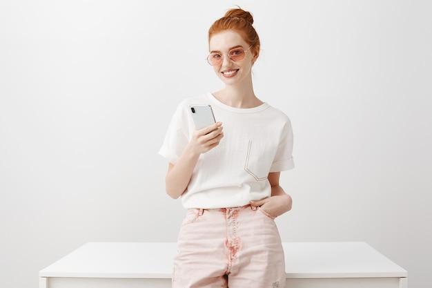 Aantrekkelijke stijlvolle roodharige meisje in zonnebril met behulp van mobiele telefoon