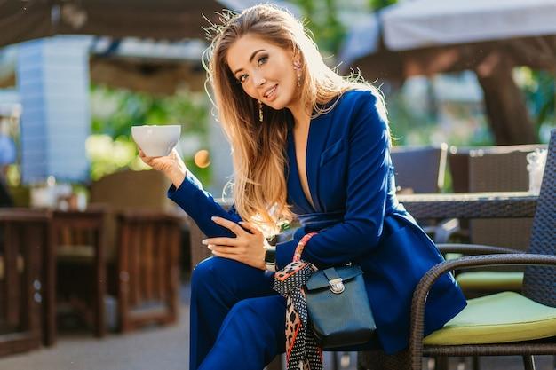 Aantrekkelijke stijlvolle vrouw gekleed in blauwe elegante pak zittend aan tafel in café kopje cappuccino drinken
