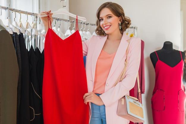 Aantrekkelijke stijlvolle vrouw kleding in kledingwinkel kiezen